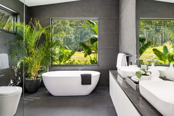 Spacious grey-wall bathroom with white tub in Kangaroo Valley House