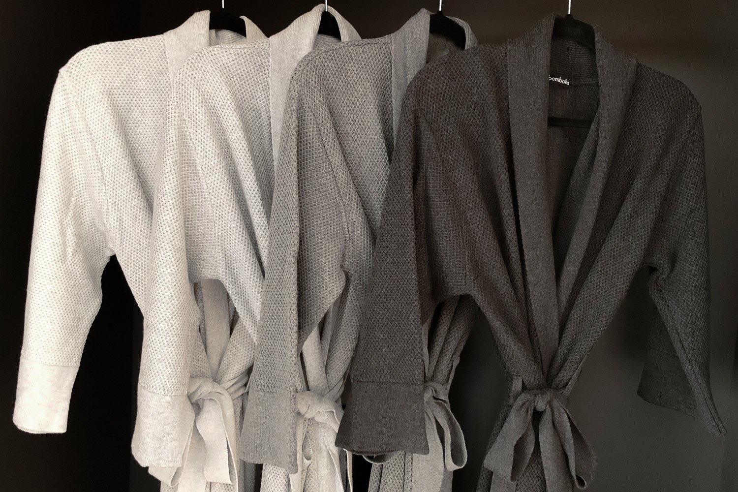 Four cotton bathrobes in shades of white and grey colours